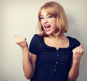 Happy excited winner woman with opened mouth. Happy blond young satisfacted girl showing the gesture yes by fists. Toned closeup portrait poster