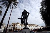 A statue stands outside the bull fighting ring in Seville, Spain poster