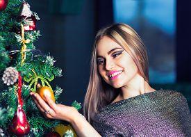 Beautiful Woman Decorating Christmass Tree
