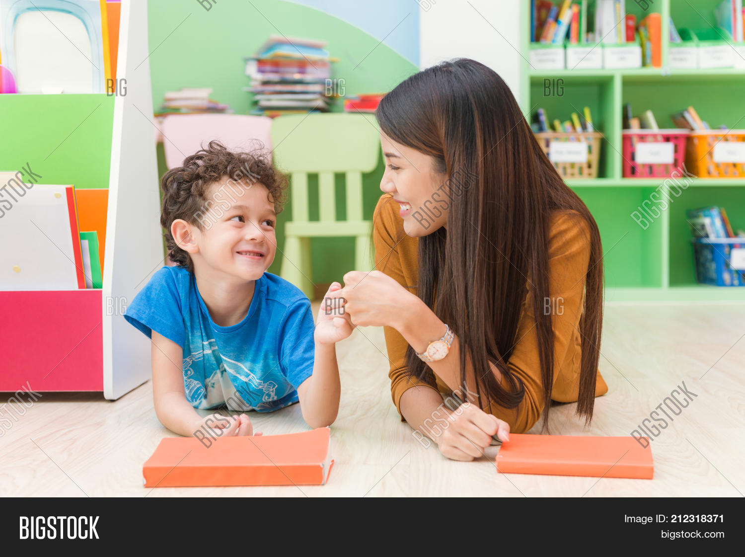 Young asian woman teacher teaching american kid in kindergarten classroom  with happiness and relaxation. Education