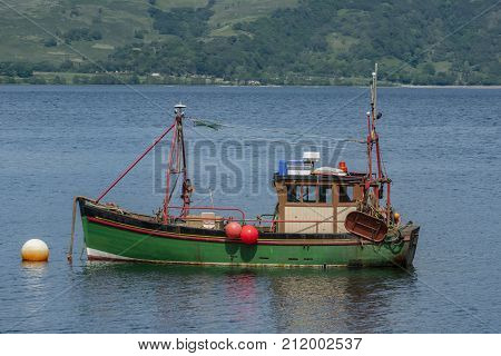 Fishing boat in an estuary in Scotland with green hillside in the background