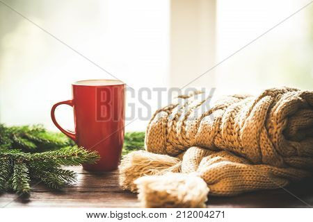 Christmas Hot Coffee In Red Cup On Wooden Table On A Frosty Winter Day Window Background With Knitte