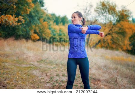 Caucasian Jogger Girl Performs Warming-up With Hands  Before Jogging