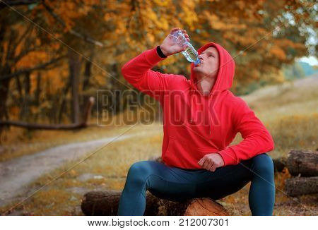 Young Athletic Runner Drink Water From The Bottle