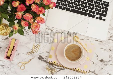 Feminine Workplace Concept. Freelance Workspace In Flat Lay Style With Laptop, Coffee, Flowers, Gold