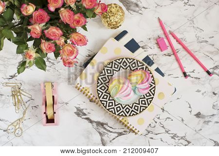 Feminine Workplace Concept. Freelance Workspace In Flat Lay Style With Sweets, Flowers, Notebooks On
