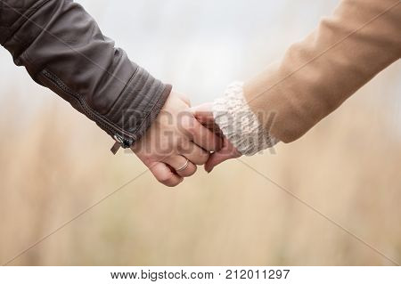 Closeup of loving couple holding hands while walking married man autumn background.