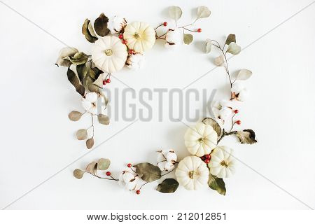 Frame of white pumpkins red berries and eucalyptus branches on white background. Flat lay top view autumn fall composition.