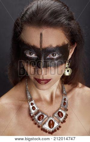 Beauty, fashion portrait. Portrait of a beautiful woman with black skin stripe, beautiful jewelry. Body painting project. Make-up and jewelry.