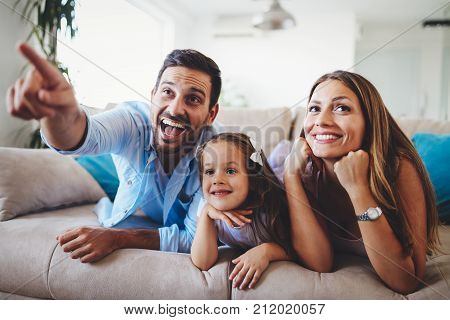 Happy family watching television together at their home