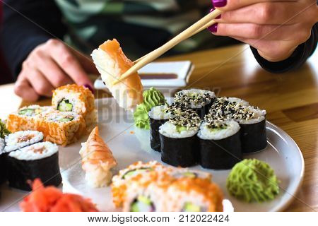 Sushi And Rolls, Japanese Cuisine, A Girl Eating Sushi