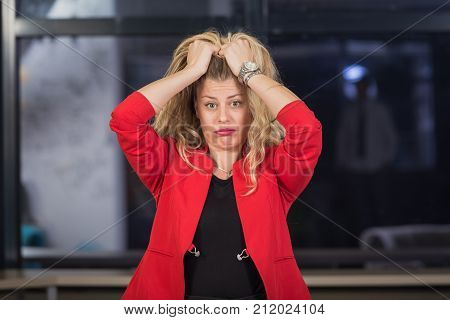 Portrait of depressed businesswoman pulling her hair out. She is upset because of business problems.