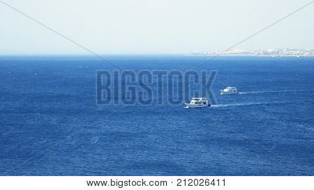 Powerboats and ship s are sailing along the tropical seashore. Having a good time in tropical sea or ocean.