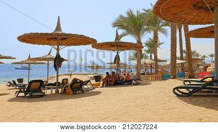 Sharm-El-Sheikh, Egypt - August 27, 2017: People are having fun at the beach lying under the beach umbrellas. Tropical sea resort beach recreation. Lazy summer vacation human behavior.