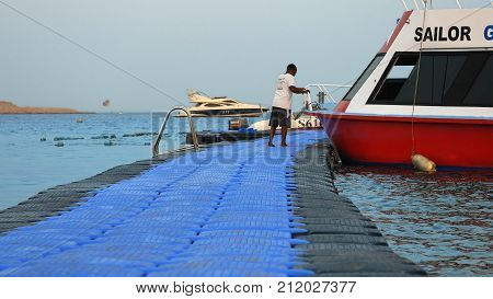 Sharm-El-Sheikh, Egypt - August 27, 2017: Touristic ship is mooring up at the floating jetty dock at the tropical resort beach at sunset. Seaside area for vacation and summer relaxation.