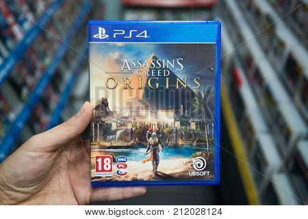 Bratislava, Slovakia, november 3, 2017: Man holding Assassin's creed Origins videogame on Sony Playstation 4 console in store