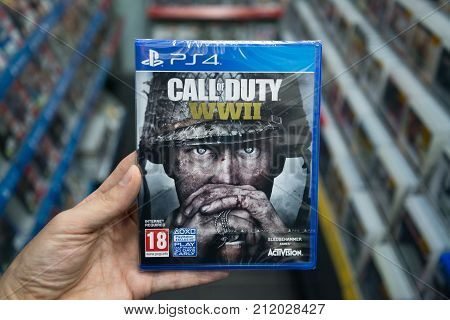 Bratislava, Slovakia, november 3, 2017: Man holding Call of duty World War 2 videogame on Sony Playstation 4 console in store
