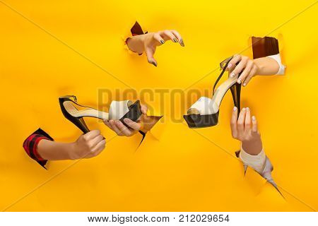 The female shoe on hand through a torn yellow paper. The sale, shopping and black friday concept