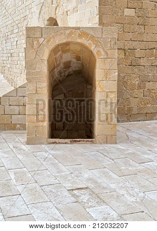 Ancient crypt entrance bricks stone wall and tiled stone floor beside Kayet bay castle Alexandria Egypt