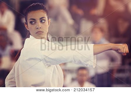 A black belt girl is performing a kata at a karate competition. People out of focus in background.
