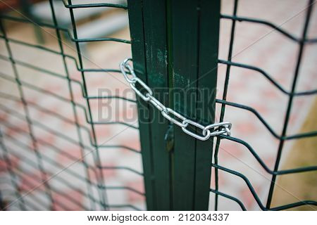Close Up Metallic Net-shaped Green Fence That Closed And Wrapped By Chain
