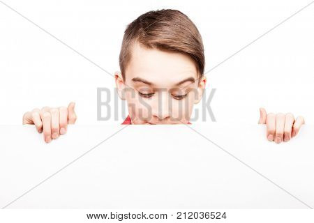 Cute teenager boy looking down at blank white board or banner that he holds in his hands Isolated on white background