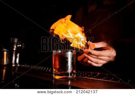 Glass of fiery cocktail on the bar counter against the background of bartender with fire