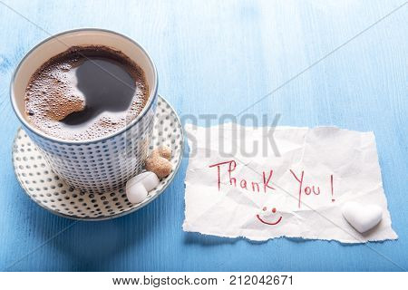 Coffee cup and cute thank you note - Paper note with a thank you message and a smiley face a cup of hot aromatic coffee with pieces of heart shaped sugar on a blue wooden table on a sunny day.