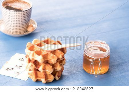 Sweet snack and a missing you note - Tasty breakfast with fresh waffles with honey a hot cup of coffee and a cute paper note with the message missing you under the morning light on a blue table.