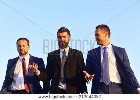 Business and success concept. Board of businessmen wear suits and ties on blue sky background. Managers go ahead and talk. Leaders with beard and smiling faces control project.