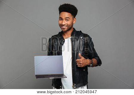 Portrait of a happy young african man in leather jacket holding blank screen laptop computer while showing thumbs up gesture and looking at camera isolated over gray background