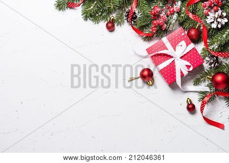 Christmas background. Snow Fir tree branch present box and xmas decorations on white table. Top view with copy space.