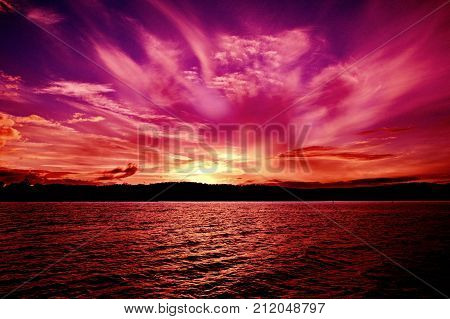 Spectacular vivid pink Orange Violet Ocean Sunset with water reflections. Photographed in Lake Macquarie NSW Australia.