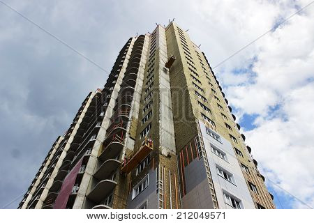 worker in yellow front suspended cradle on a newly built high-rise building.