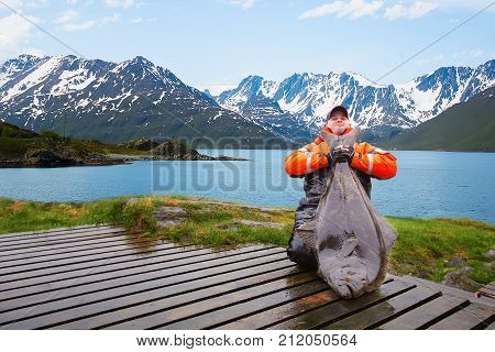 Man fisherman with a big fish Halibut. Behind the beautiful landscape. Norway