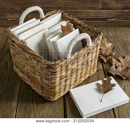 books in a white cover in a wicker basket on a wooden background and a table row of autumn leaves