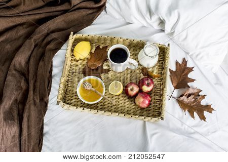 wicker tray with food and drink on a white bed