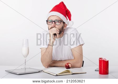 Handsome guy in red hat celebrates New Year alone at office due to circumstances. All he has is milk at fridge and apple. Sad and lonely young Caucasian businessman spending Christmas Eve in bad mood