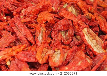 Traditional dried red tomatoes background close up.