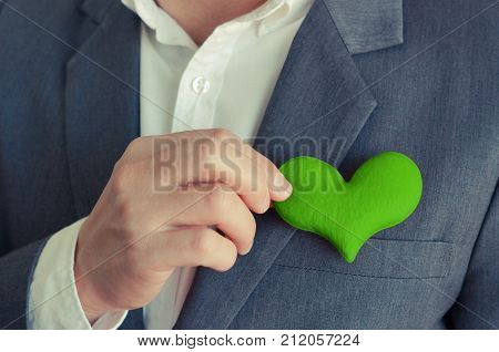 Businessman holding a green heart / Business with corporate social responsibility and environmental concern poster