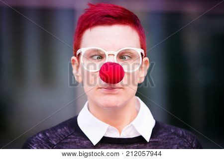 portrait of red-haired beautiful woman with red nose and cross-eyed