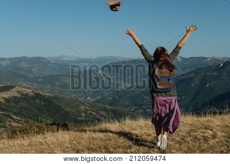 Woman Back Traveler Tosses A Hat Against The Background Of The Mountains.  Freedom Concept