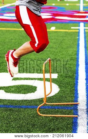 A high school football player is cross training by jumping over orange mini hurdles at practice on a green turf field.