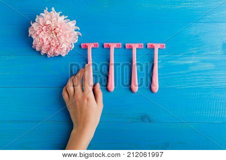 Set for hair removal. Blue and pink womans razor on the blue background. Beautiful roses and pionies lying near the razors. Close-up of objects.
