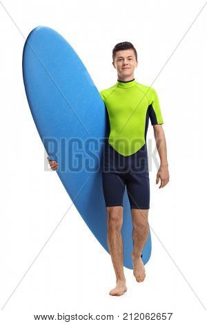 Full length portrait of a teenage surfer holding a surfboard and walking towards the camera isolated on white background