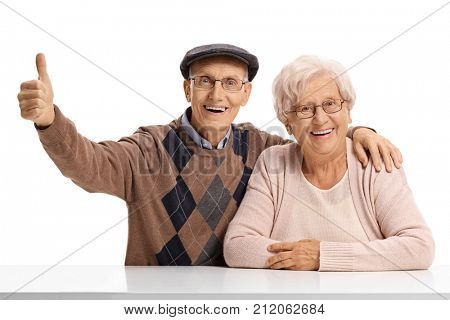 Elderly man and an elderly woman sitting at a table with the elderly man holding his thumb up isolated on white background