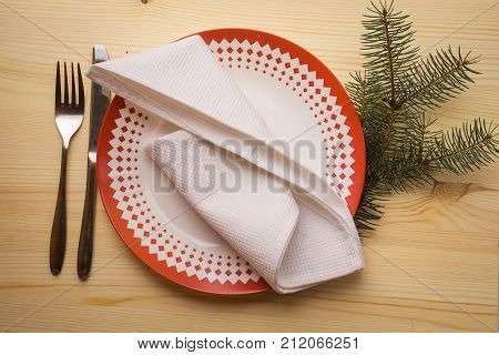 Christmas table place setting with dinner plates, napkin, cutlery, fir on wooden background