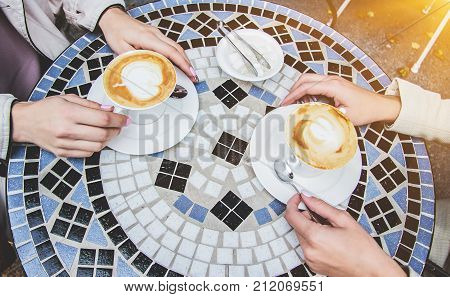 Top View Of Female Hands Holding Cups Of Coffee. Enjoying Coffee Outdoors.