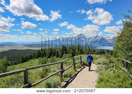 Boy hiking with jackson lake and mount teton view in summer
