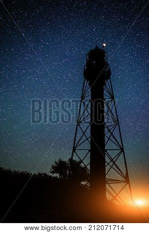 Silhouette Of The Old Lighthouse And Trees Against The Background Of The Starry Sky With Sparkle Of